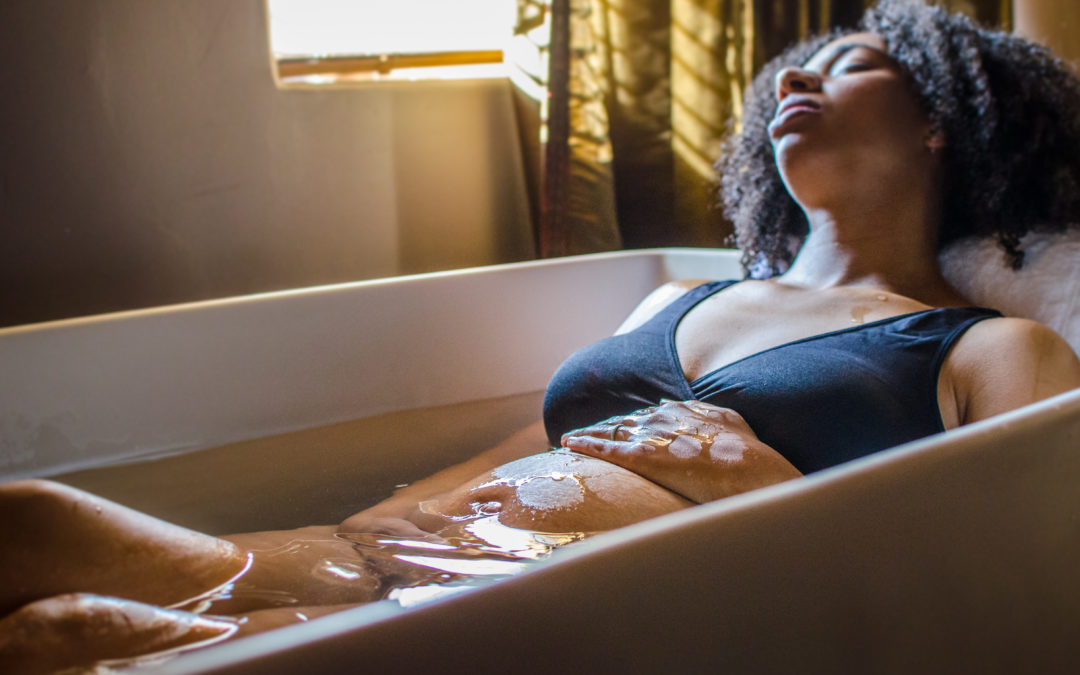 A woman in labor in a bath tub at Babymoon Inn Birth Center in Phoenix